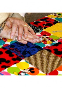 Hands tying knots in a quilt